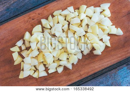 sliced raw potatoes on a cutting Board on an old rustic wooden table. top view close up tinted photo