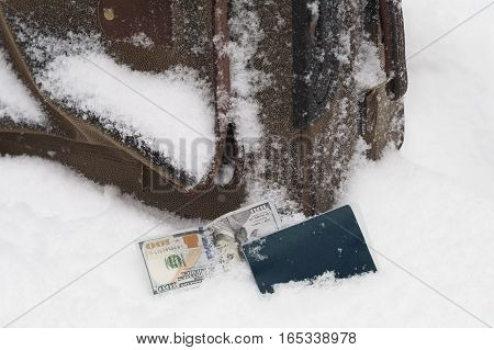 Lost abandoned luggagge covered with ice and snow with passport and cash in the foreground