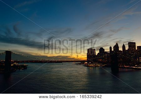 View of Lower Manhattan with Brooklyn Bridge at sunset.