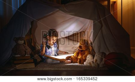 child girl reading with book and flashlight and teddy bear in tent. before going to bed