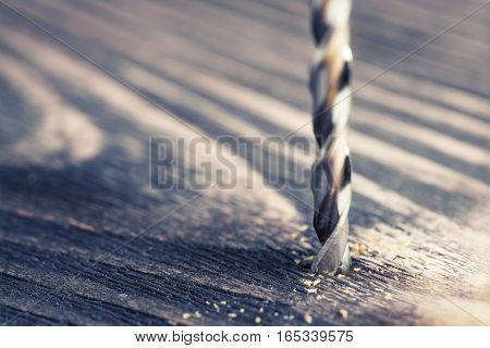 drill bit drilling hole in wooden plank