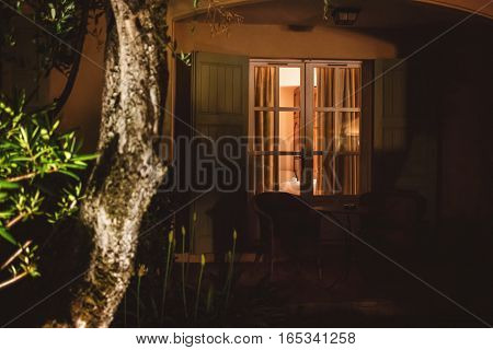 Door of house at night. Table and two chairs outdoors. Return home by midnight.