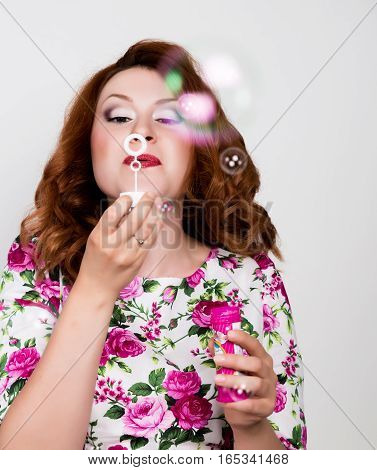 young stylish red-haired woman with curly hair and pretty face posing and blow bubbles. expresses different emotions.