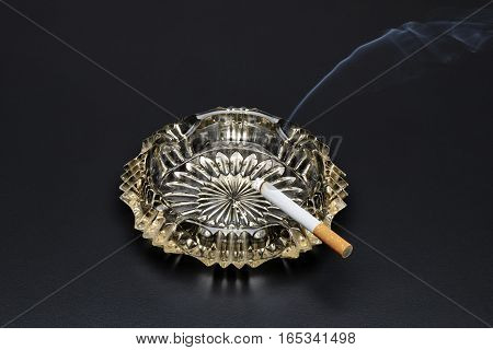 Burning Cigarette With Smoke In Ashtray