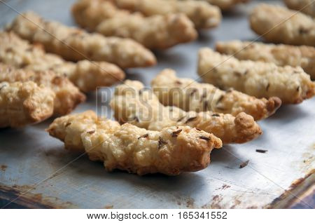 Homemade cookies with cheese and caraway seeds on a metal baking sheet close-up.