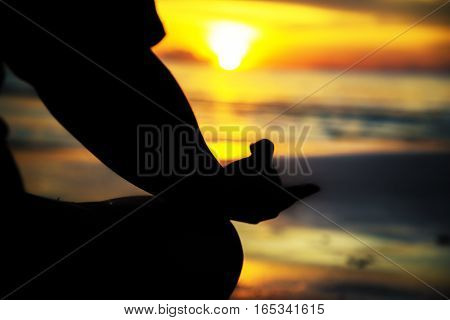 Sillouete woman sit for meditation in sunset