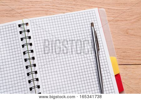 Notepad and personal diary or organizer, paperwork concept. Office or student's device on wooden desk. Working table top view. Education background with copy space on paper