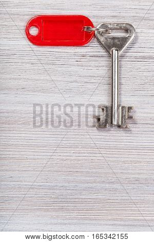 Big Key With Red Key Chain On Wooden Surface