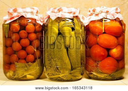 Three Canned Fresh Vegetables. Tomatoes Cherry Cucumbers And Tomatoes In Big Glass Jar On Beige Background.