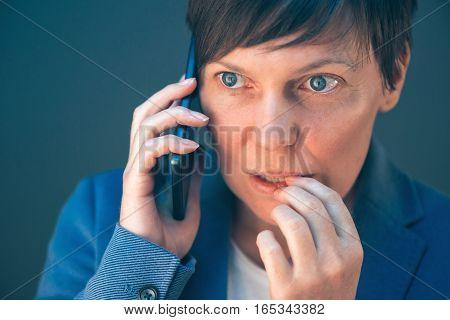 Nervous businesswoman bites fingernails during telephone conversation on mobile phone