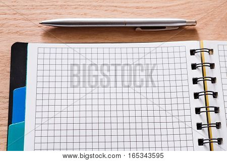 Notepad and personal diary or organizer closeup, writing to do list concept. Office or student's device on wooden desk. Working table top view. Education background with copy space on paper
