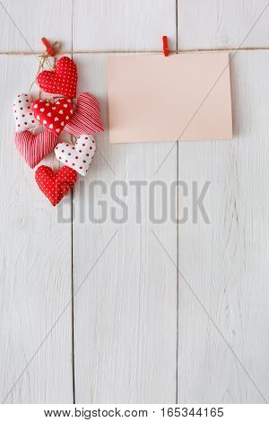 Valentine background with sewed pillow diy handmade hearts and empty greeting card on red clothespins at rustic white wood planks. Happy lovers day mockup, copy space, vertical