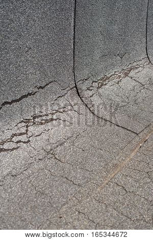 Damaged insulation layer of the roof. Destruction flat roof due to temperature changes. Damaged waterproofing flat roof. Crack roofing felt. Damaged roofing felt. Old roofing felt. Waterproofing.