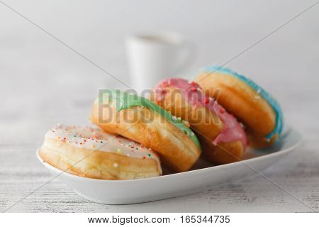 Few Colorfull Donuts Lay On Plate With Cup Of Espresso