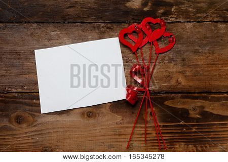 Red hearts and paper on the wooden board