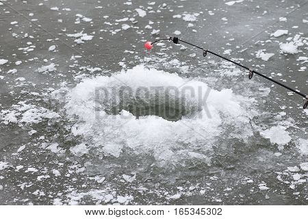 A hole in ice and fishing rod