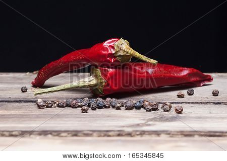 Two red peppers chilli and flavoring on the wooden table