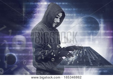 Hooded Hacker Man With Vendetta Mask Typing On Virtual Keyboard