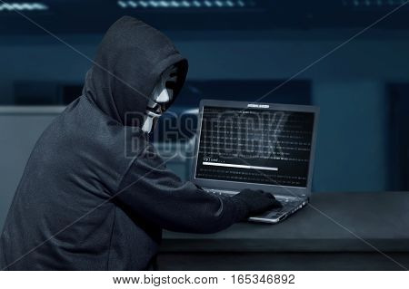Hacker Man Wearing Mask Using Laptop To Upload Computer Virus