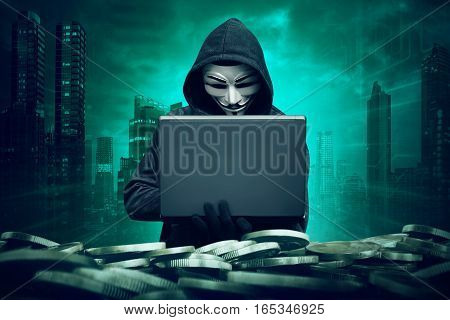 Hooded Hacker With Mask Using Laptop To Hacking Bank