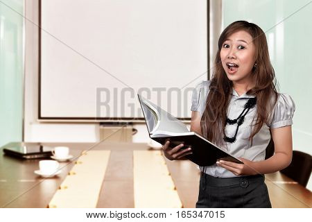 Portrait asian business woman looking surprised while holding document over meeting room at office