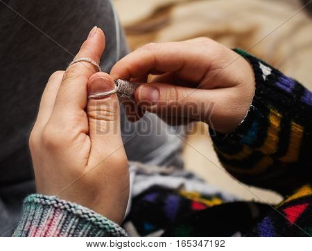 close up of woman hands knitting with needles and grey yarn