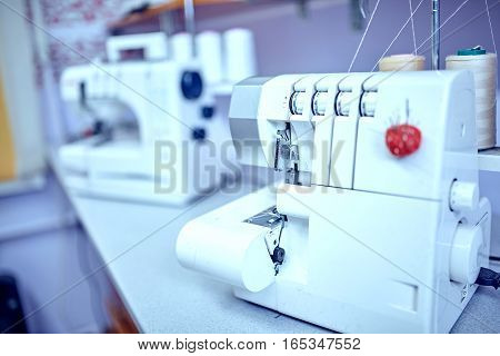 Workplace of tailor - sewing machine rolls of of thread fabric scissors.