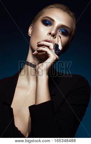 Beautiful girl in a black dress, straight hair and trendy makeup. Glamour beauty face. Photos shot in the studio.