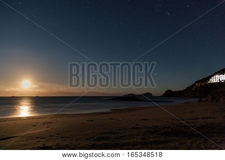 A moonlit beach with the stars bright in the night sky