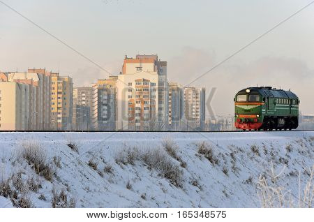 Riding old locomotive on the background of modern district in the winter.