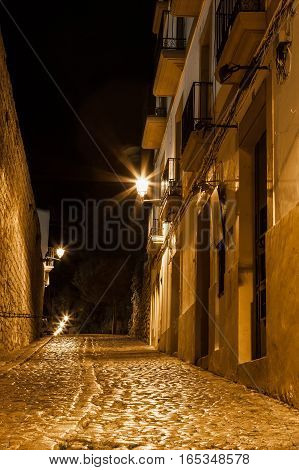 A narrow Spanish cobbled street in the night