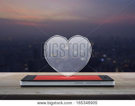Love heart icon with copy space on modern smart phone screen on wooden table over blur cityscape on warm light sundown Internet online love connection Valentines day concept