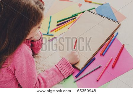 Girl drawing picture with colored markers, crayons and pencils. View from above, copy space on paper sheet. Creative children, child art school or courses concept
