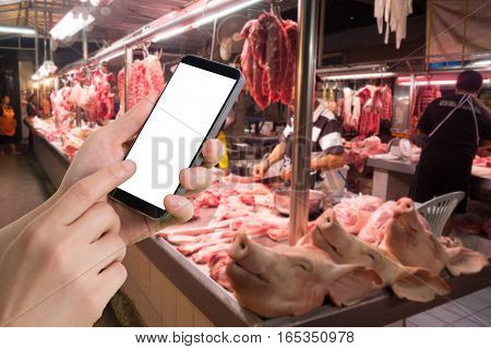 human's hand hold and touch of blank screen smartphone tablet cell phone on blurry fresh pork market. concept of products check price.