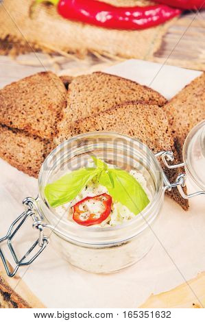 white pate with garlic and herbs in glass container