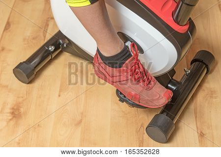 Aerial view of the woman`s leg on the exercise bike indoors. Horizontally. All potential trademarks are removed.