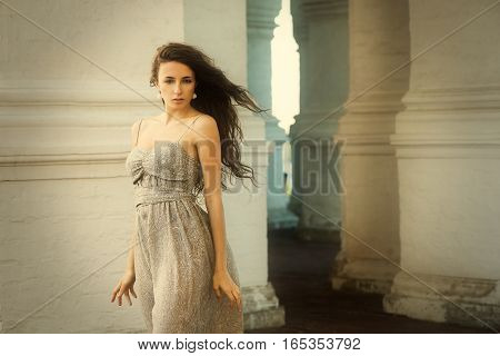 Young beautiful innocent woman with flying curly hair outdoor