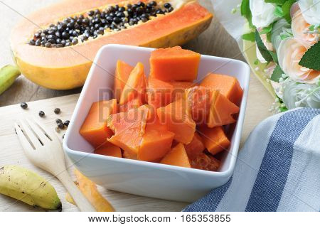 kitchen table with sliced of fresh papaya fruit on wood plate. concept of sliced tropical fruit for lose weight and health care. selective focus on top view.
