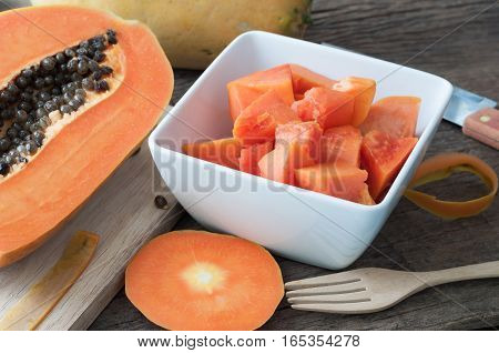 kitchen table with slice fresh papaya on wood plate Fruit for the digestive system selective focus on top view.