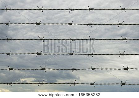 Rusty barbed wire and stormy sky background