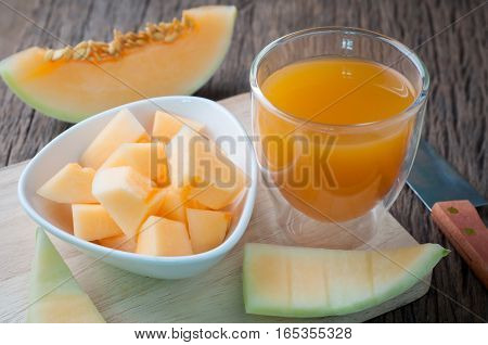 kitchen table with slice freshness cantaloupe melon and glass of juice on cutting board . healthy eating and dieting food concept of health care Image focus top view.