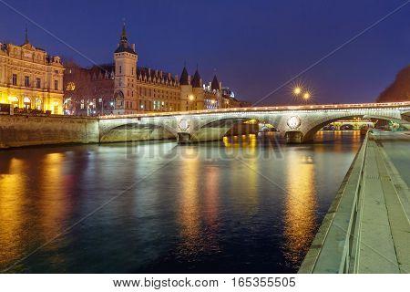 Conciergerie and Illuminated bridge Pont au Change at night, Paris, France