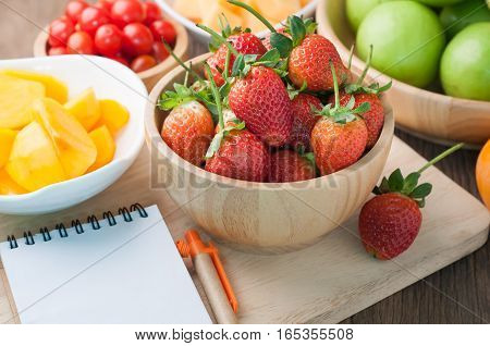 kitchen table with variety fruit strawberrydwarf tomatoesmonkey apple melon persimmon and blank screen on notepad paper. healthy eating and dieting food concept of health care. focus top view.