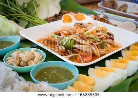 kitchen table with spicy papaya salad boiled egg and ingredient food Thai national food concept of hot asian food. Image focus top view.