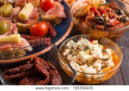 Variety of Mediterranean snacks on old wooden table. Tapas or antipasti