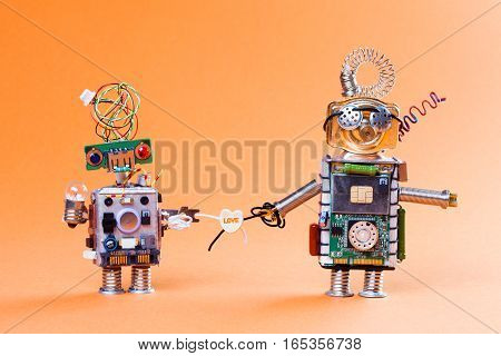 Robot love story concept. Funny circuit socket toys with lamp bulb and love heart symbol. Cute faces, blue red eyes and glasses. light gradient orange color