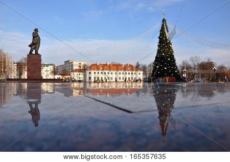 Grodno, Belarus - December 19, 2013: Square with Lenin's monument and Christmas tree. Reflection on the marble surface.