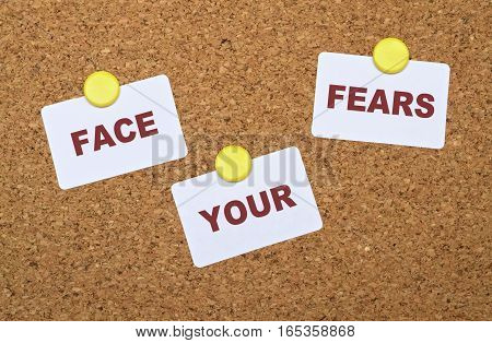 Text Face Your Fears on white stickers pinned on cork board