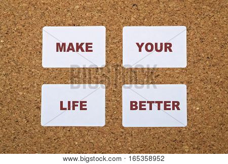 Text Make Your Life Better on white stickers pinned on cork board