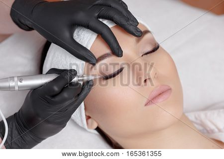 Side view of cosmetologist wearing black gloves making permanent makeup for young beautiful woman. Using specialty tool for tattoo. Client lying at beauty salon with closed eyes.